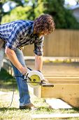 Carpenter using circular saw to cut plank while building a deck