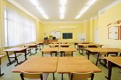 Empty classroom with wooden desks, white and green chalk boards in school.