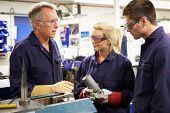 foto of overalls  - Engineer Working With Apprentices On Factory Floor - JPG