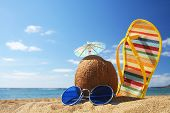 stock photo of summer beach  - stilllife on the beach with sunglasses cocktail in coconut and flip flop - JPG