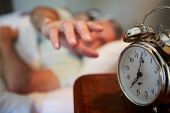 pic of early 50s  - Couple In Bed With Man Reaching To Switch Off Alarm Clock - JPG