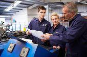 stock photo of bend  - Engineer Teaching Apprentices To Use Tube Bending Machine - JPG