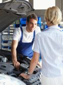 pic of auto repair shop  - mechanic talking with female client in auto repair shop - JPG