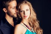pic of desire  - Portrait of a beautiful young couple in love posing at studio over dark background - JPG
