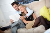 picture of reading book  - Beautiful couple smiling and reading on the sofa - JPG