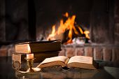 picture of scriptures  - An open Bible with a burning candle in front of fireplace - JPG