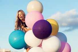 stock photo of latex woman  - Happy young girl with big colorful latex balloons - JPG