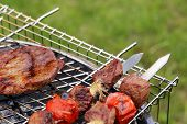 stock photo of grilled sausage  - Cooking on the barbecue grill assortment sausages steak and skewers - JPG