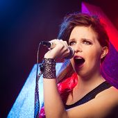picture of pop star  - Young pop star girl singing on stage close up.