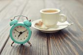 picture of analog clock  - Vintage alarm clock with cup of coffee on wooden background