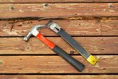 pic of pry  - Horizontal photo of old hammer and pry bar next to rotting wood on cedar wooden deck - JPG