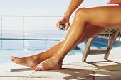 foto of suntanning  - Woman applying suntan spray onto her legs. Female sitting on recliner chair by the swimming pool sunbathing.