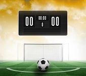 stock photo of football pitch  - Black scoreboard with no score and football against football pitch under yellow sky - JPG