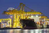 stock photo of shipyard  - Cargo ship and crane at port reflect with water twilight time - JPG