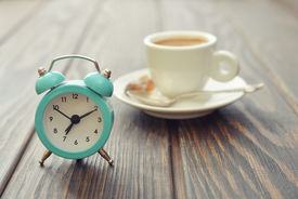 stock photo of analog clock  - Vintage alarm clock with cup of coffee on wooden background  - JPG