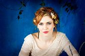 stock photo of cuff  - Romantic portrait of a beautiful woman with red hair and flowers in her hairstyle - JPG