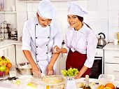 stock photo of pastry chef  - Happy woman and man in chef hat cooking dough  - JPG