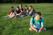 picture of peer-pressure  - Lonely teen male sitting away from group - JPG