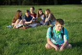 image of peer-pressure  - Lonely teen male sitting away from group - JPG