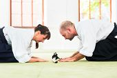 image of aikido  - Man and woman take a bow to greet at Aikido martial arts school  - JPG