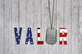 stock photo of tribute  - Military dog tags with flag font for armed forces valor on weathered wood background - JPG