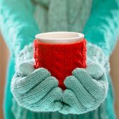 image of hot-weather  - Woman holding winter cup close up on light background - JPG