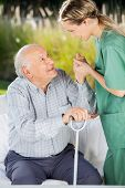 stock photo of hospice  - Side view of female caretaker helping senior man to get up from couch - JPG