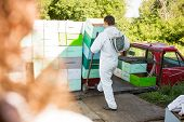 image of bee keeping  - Rear view of male beekeeper loading stacked honeycomb crates in truck - JPG