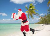 Постер, плакат: christmas holidays travel and people concept man in costume of santa claus running with gift box