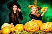 picture of teen smoking  - Two pretty teen girls in a costumes of witches standing with pumpkins over dark smoky background - JPG