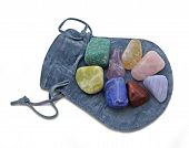 foto of chakra  - Chakra Crystal Set of  eight rainbow colored stones placed on a blue cloth pouch on a white background - JPG