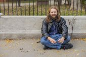 picture of long beard  - Blond long hair and beard young adult hipster man listening music. Outdoor, urban scene. ** Note: Shallow depth of field - JPG