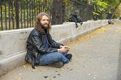 stock photo of long beard  - Blond long hair and beard young adult hipster man listening music. Outdoor, urban scene. ** Note: Shallow depth of field - JPG