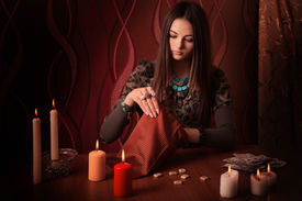 picture of divine  - Young woman with runes and divination cards in room - JPG