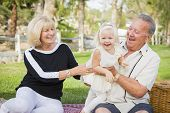 picture of granddaughter  - Affectionate Granddaughter and Grandparents Playing Outside At The Park - JPG