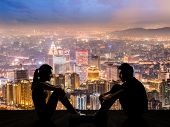 image of ladies night  - Silhouette of young couple face to face sit on ground in the city night - JPG