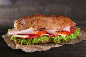 stock photo of oblong  - Fresh and tasty sandwich with ham and vegetables on paper on wooden background - JPG