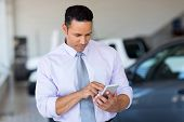 stock photo of showrooms  - mid age car salesman using cell phone in showroom - JPG
