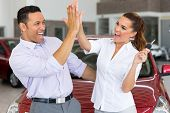 pic of excitement  - excited mid age couple giving high five after buying new car - JPG