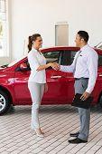 picture of handshake  - attractive young woman handshaking with car salesman in showroom - JPG