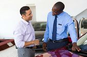 stock photo of showrooms  - african car salesman selling a car to mid age customer in showroom - JPG