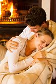 image of snuggle  - affectionate couple wrapped in blanket at home by fireplace - JPG