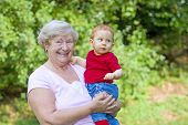 picture of nana  - Grandmother holding happy grandson in sunny garden - JPG