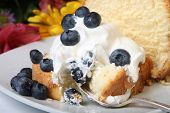 image of pound cake  - Slice of pound cake with whipped cream topped with blueberries and flowers in the background
