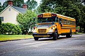 stock photo of driving school  - Yellow school bus driving along street - JPG