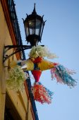picture of pinata  - Colorful mexican pinata hanging in a streetlamp  - JPG