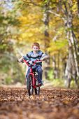stock photo of bike path  - Young boy with bike on path during the autumn - JPG