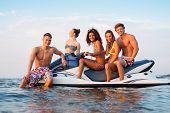 foto of ski boat  - Group of multi ethnic friends sitting on a jet ski - JPG
