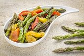 pic of teardrop  - roasted asparagus salad on a teardrop shaped bowl against white painted rustic wood with fresh asparagus - JPG