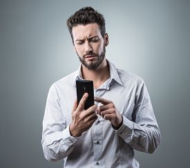 picture of disappointed  - Disappointed young man typing on his touch screen smartphone - JPG